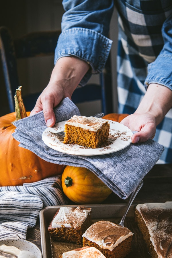 Hands holding a plate with a square of pumpkin bars on it.