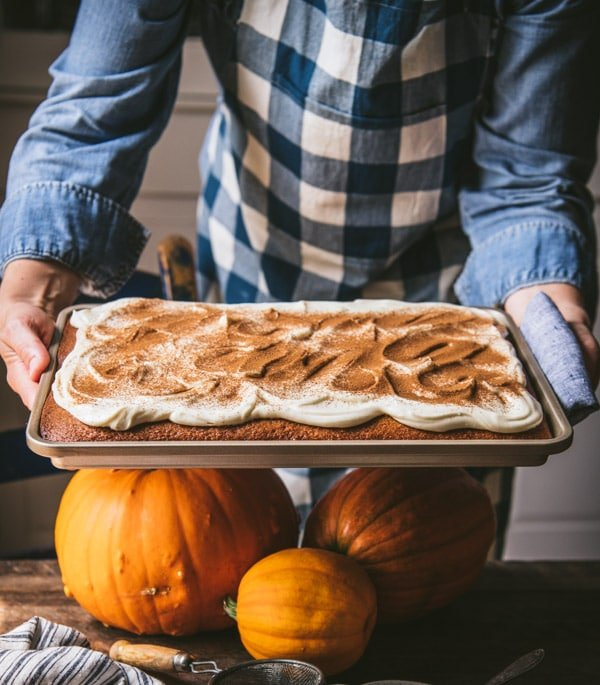 Hands holding a tray of pumpkin spice bars with cream cheese frosting and a dusting of cinnamon.