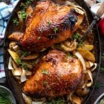 Overhead shot of roasted chicken breast with molasses, apple cider sauce and apples and onions in the pan