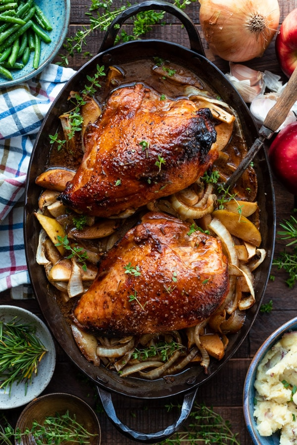 Overhead shot of oven roasted chicken breast with apples and onions in a cast iron pan