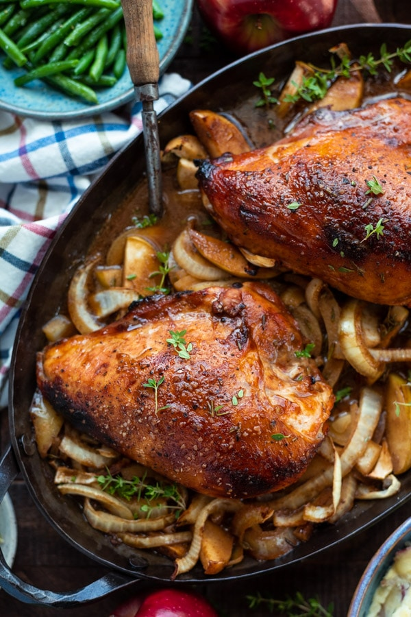 Overhead shot of a pan of roasted chicken breast with apples and onions