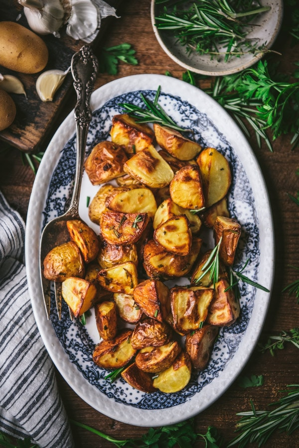 Overhead shot of rosemary roasted potatoes on a blue and white platter