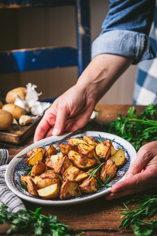 Hands serving a plate of oven roasted rosemary potatoes