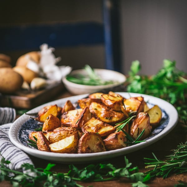 Plate of garlic rosemary roasted potatoes on a wooden table
