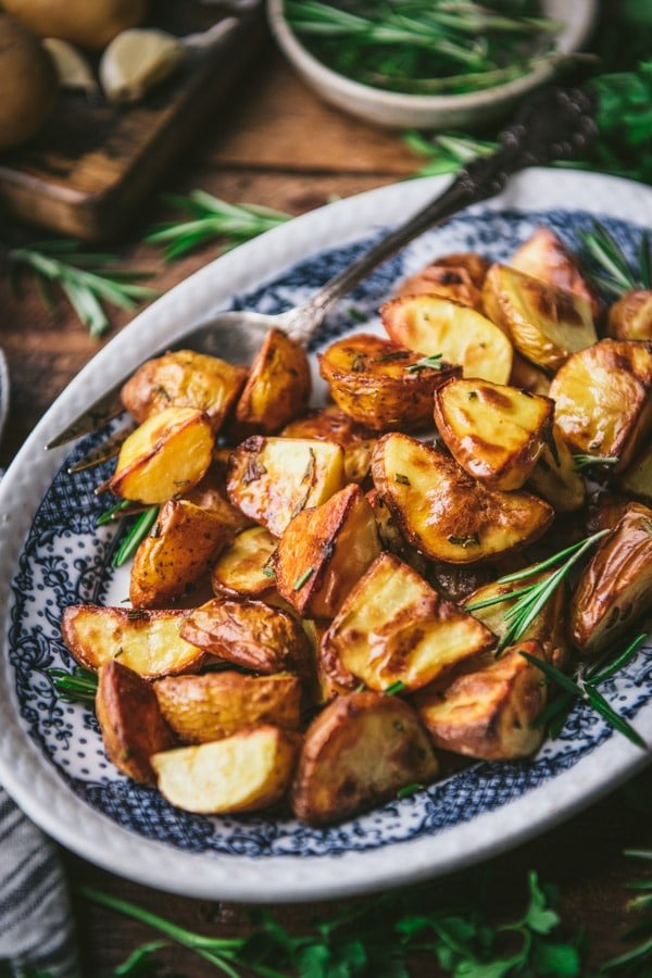Side shot of crispy roasted potatoes on a blue and white platter