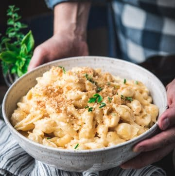 Bowl of shell mac and cheese with toasted breadcrumbs on top