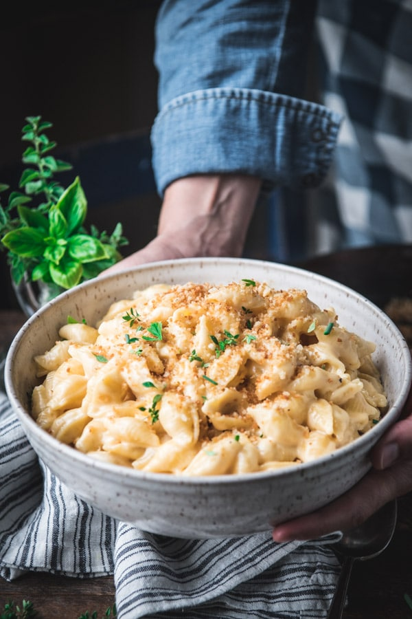 Hands holding a bowl of homemade shells and cheese