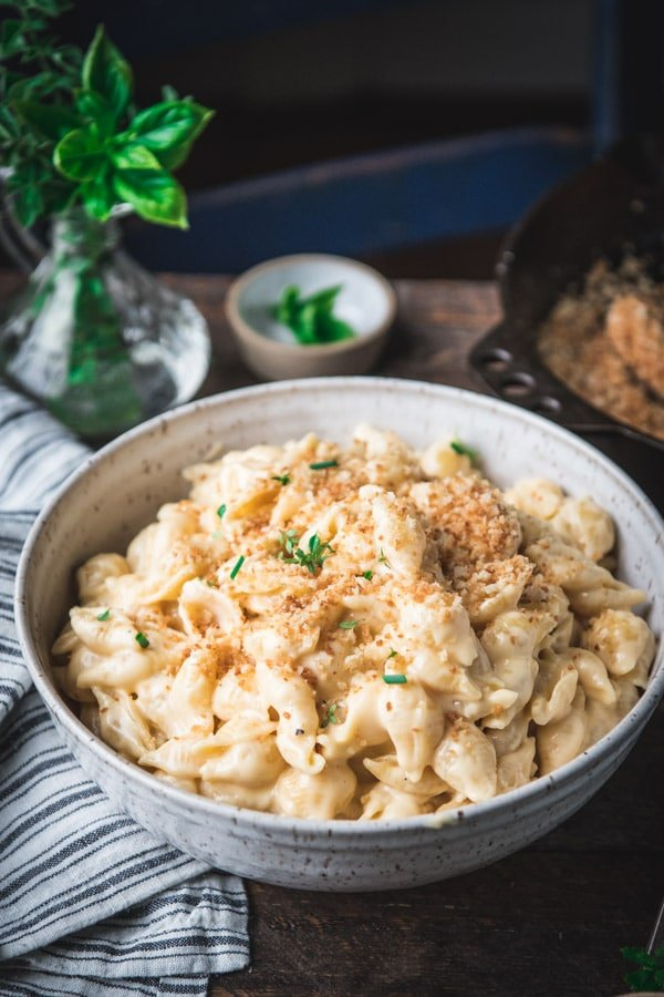 Shell mac and cheese in a bowl with toasted breadcrumbs and fresh herbs on top