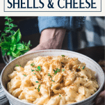Hands holding a bowl of homemade Velveeta shells and cheese with text title box at top