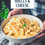 Hands holding a bowl of shells and cheese recipe with text title overlay