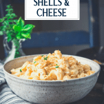Side shot of a bowl of homemade Velveeta shells and cheese with text title overlay