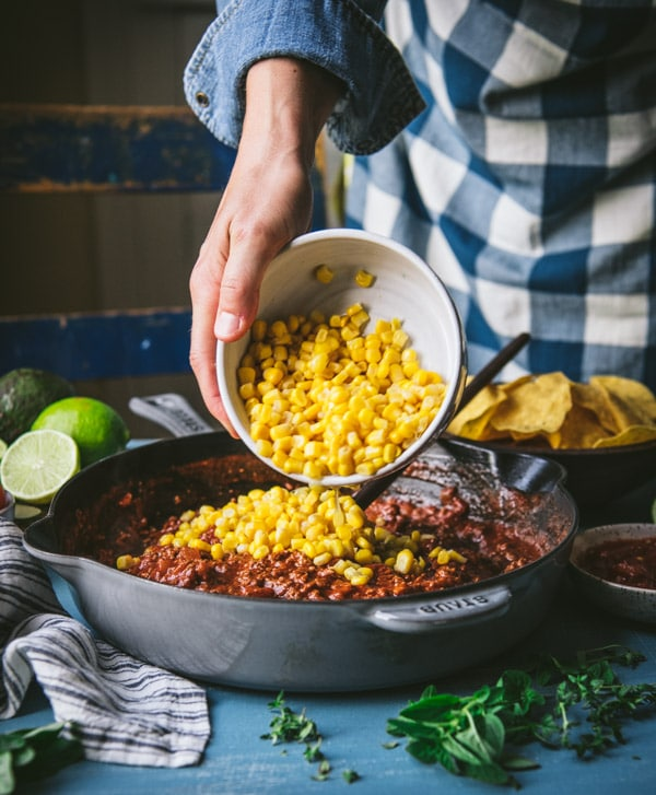 Adding corn to a skillet with ground beef