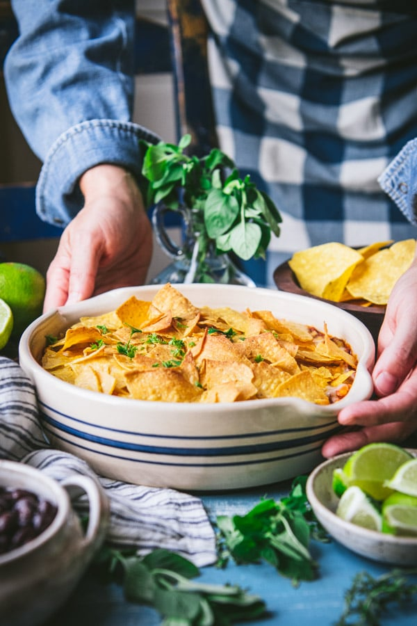 Hands placing an easy taco bake casserole on a table