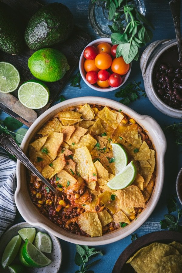 Overhead shot of taco casserole with tortilla chips on a blue table