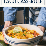 Hands serving ground beef taco casserole with text title box at top