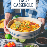 Hands serving easy taco bake casserole with toppings and text title overlay
