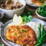 Close up side shot of pork schnitzel with mushroom gravy and a side of rice