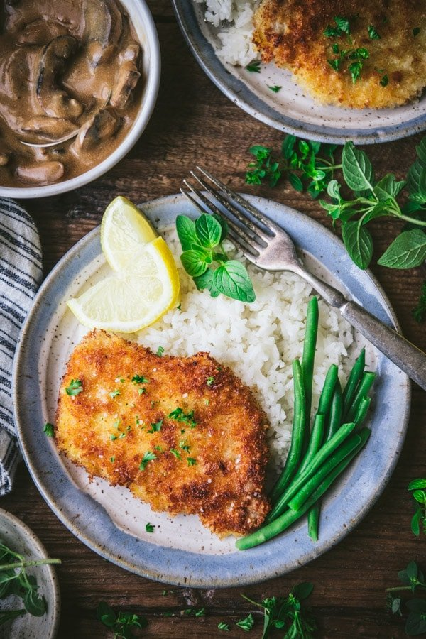 Overhead image of a plate of pork schnitzel with lemons rice and green beans