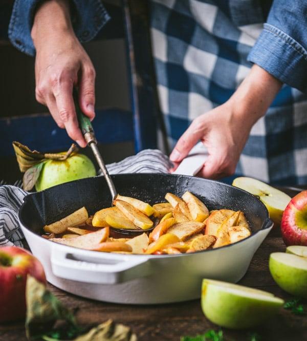 Stirring a pan of baked cinnamon apple slices