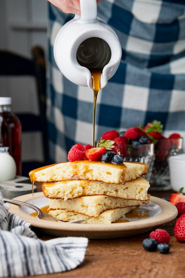 Pouring syrup over a stack of baked pancakes