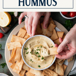 Overhead image of hands dipping pita chips in the best hummus recipe with text title box at top
