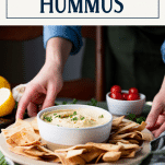 Hands serving a tray of creamy hummus with a side of pita chips