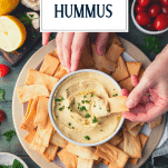 Overhead shot of hands scooping homemade hummus with pita chips and text title overlay