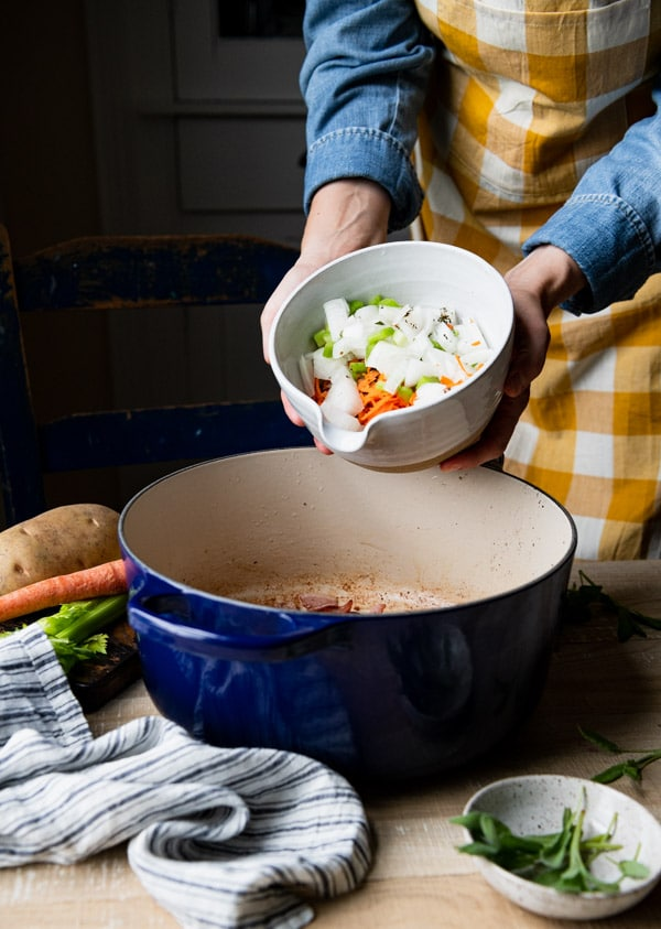 Adding diced vegetables to a blue dutch oven