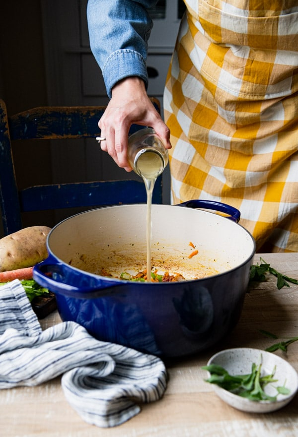 Pouring chicken broth into a pot