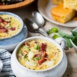 Shot of a dinner table with a bowl of easy cheeseburger soup topped with bacon and fresh herbs