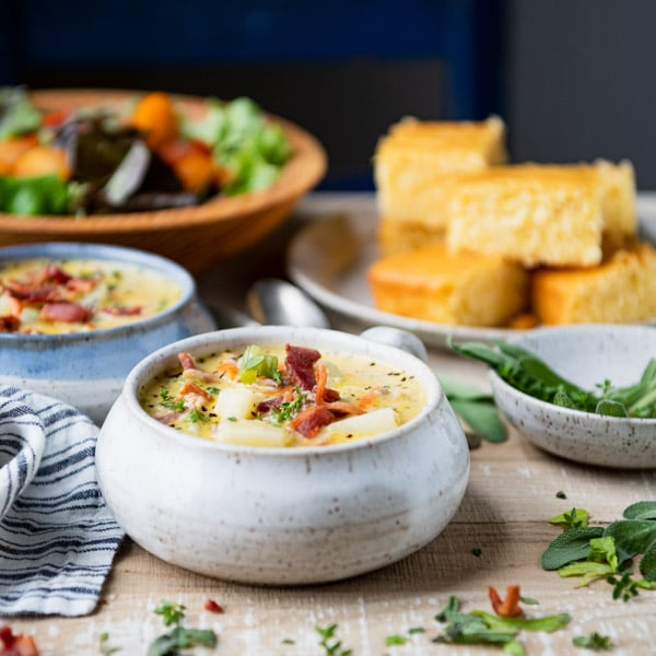 Side shot of a bowl of bacon cheeseburger soup on a white table with salad and cornbread in the background