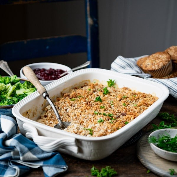 Square image of chicken and stuffing casserole on a dinner table.