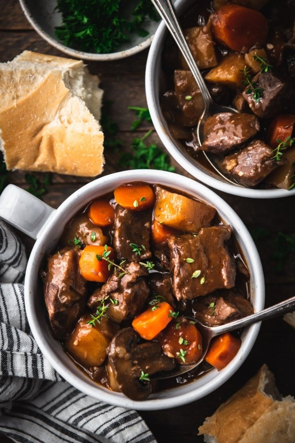The best beef burgundy stew served in two white bowls with fresh herbs for garnish
