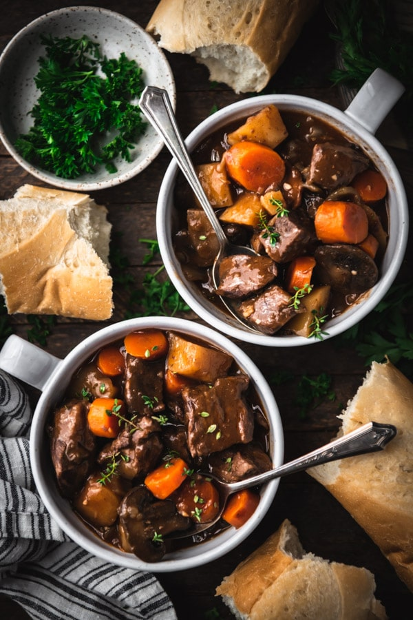 Two bowls of beef bourguignon on a dinner table with a side of bread