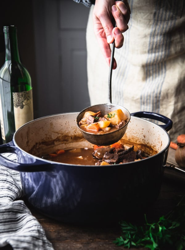 Ladle serving beef bourguignon from a Dutch oven