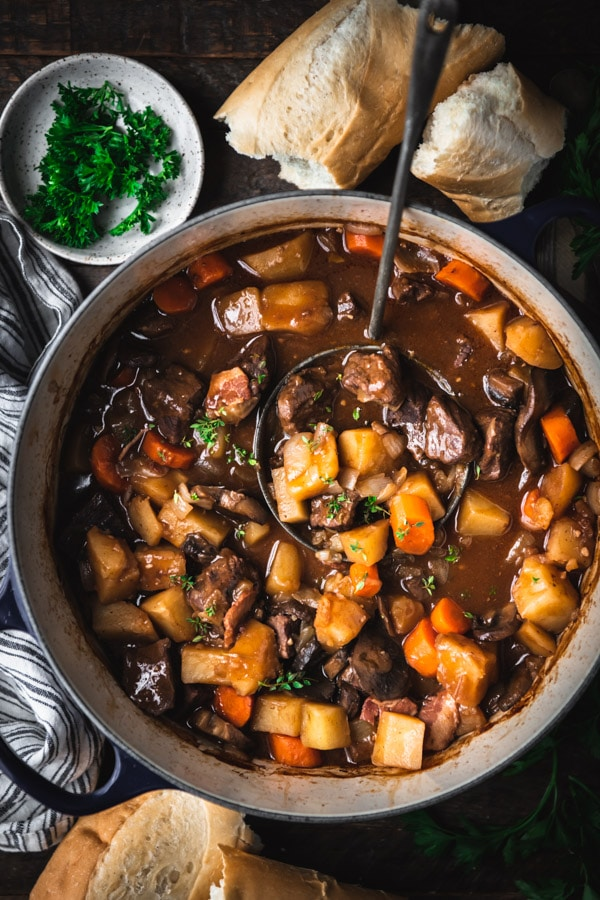 Overhead shot of a ladle in a pot of beef burgundy.