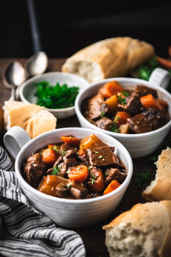 Side shot of the best beef bourguignon recipe served on a farmhouse dinner table