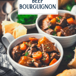 Bowl of beef bourguignon on a table with text title overlay