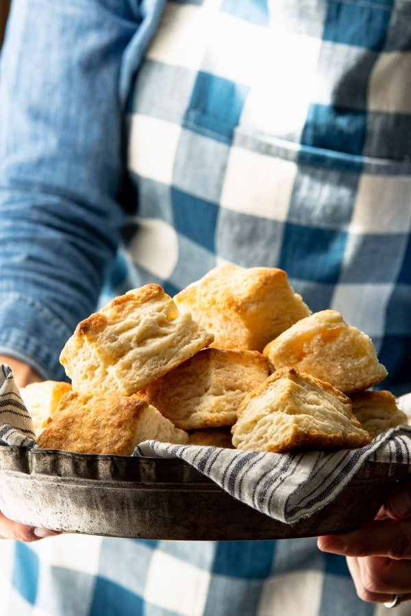 Hands holding a basket of flaky buttermilk biscuits