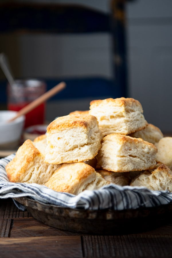 Side shot of homemade flaky biscuits in a bowl on a wooden table