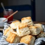 Side shot of a basket of flaky biscuits on a wooden table