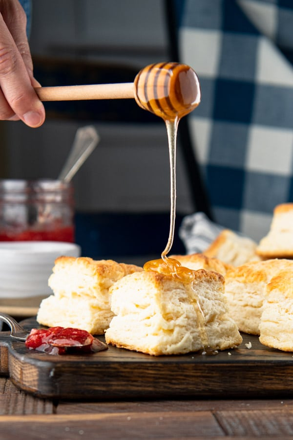 Drizzling honey on flaky buttermilk biscuits