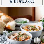 Side shot of two bowls of turkey and wild rice soup with text title box at top