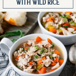 Side shot of two bowls of turkey rice soup with text title box at top