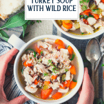 Hands holding a bowl of turkey soup with text title overlay