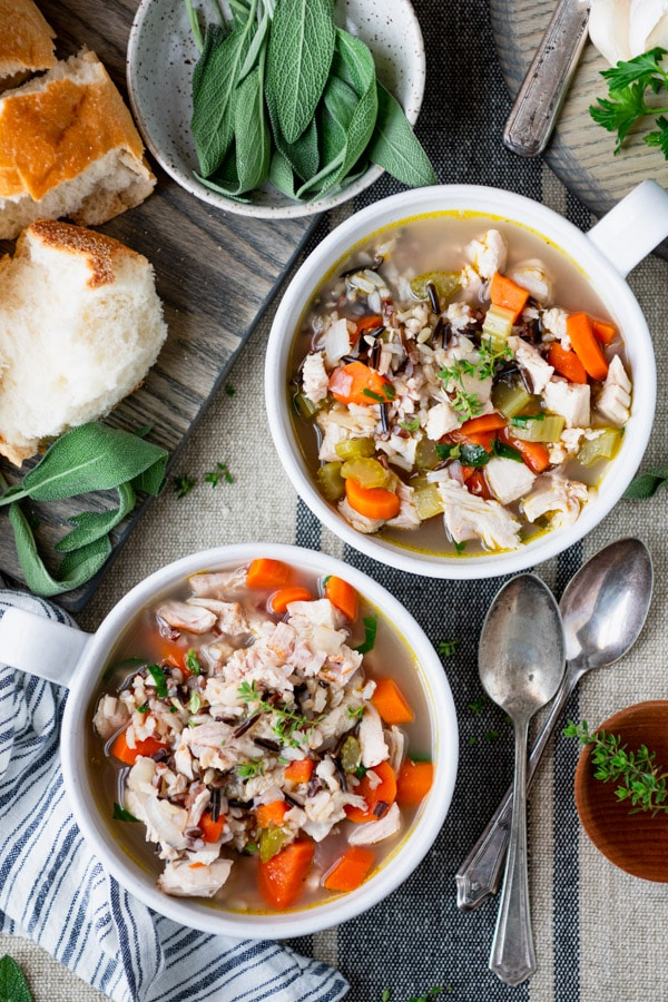 Two bowls of turkey and rice soup on a dinner table
