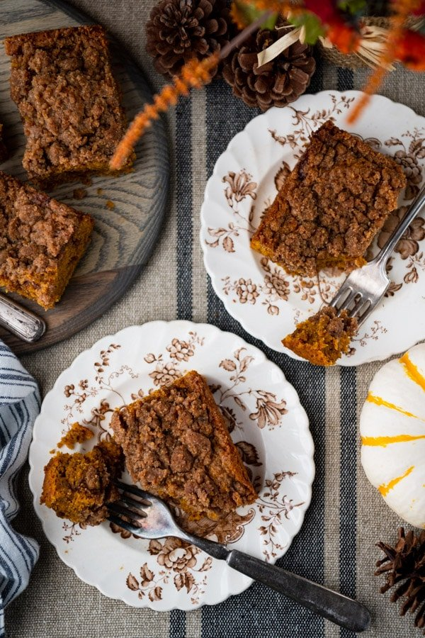 Overhead shot of a table with plates of pumpkin coffee cake with cinnamon streusel