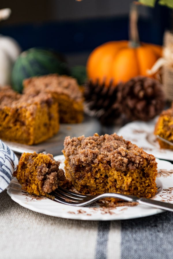 Close up side shot of a piece of pumpkin coffee cake with cake mix on a small plate