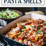 Side shot of stuffed shells with meat sauce in a pan with text title box at top