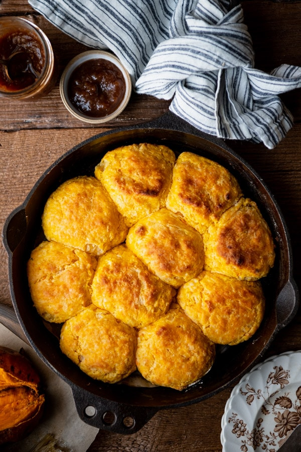 Overhead shot of a cast iron skillet full of homemade sweet potato biscuits with a side of apple butter